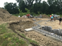 Double checking and measuring the block placement as the basement exterior walls begin.
