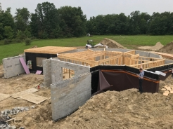 Basement walls complete and the interior walls framed out. The first floor beams are starting to get installed.