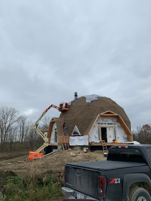 Using a JLG to get the roofers, materials, and eventually skylights up high. They installed a permanent safety ring at the very top of the dome.
