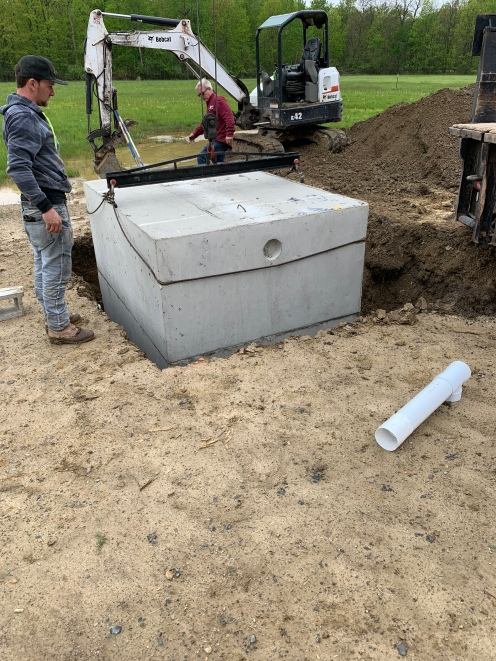 The top half of the septic tank gets set in place